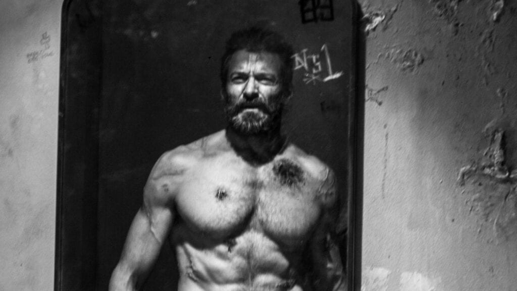 Hugh jackman looks into a mirror as Logan